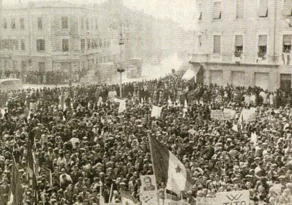 Monfalcone, 1 magio 1945, ore 14.30-15. Truppe della II Divisione Neozelandese mentre sostano nella piazza salutate dalla popolazione con cartelli che inneggiano alla Russia di Stalin e alla Jugoslavia di Tito (foto C. C. M.)