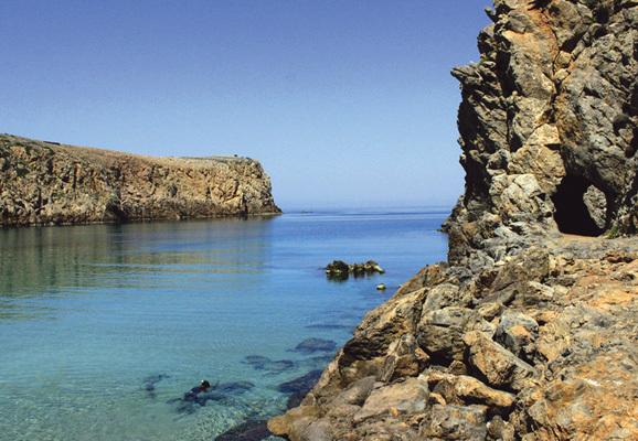 """Spiaggetta di Cala Domestica e, sulla destra, la galleria scavata dai minatori che porta alla piccola spiaggia denominata """"La Caletta"""" (ph. Michele Tomaselli)"""