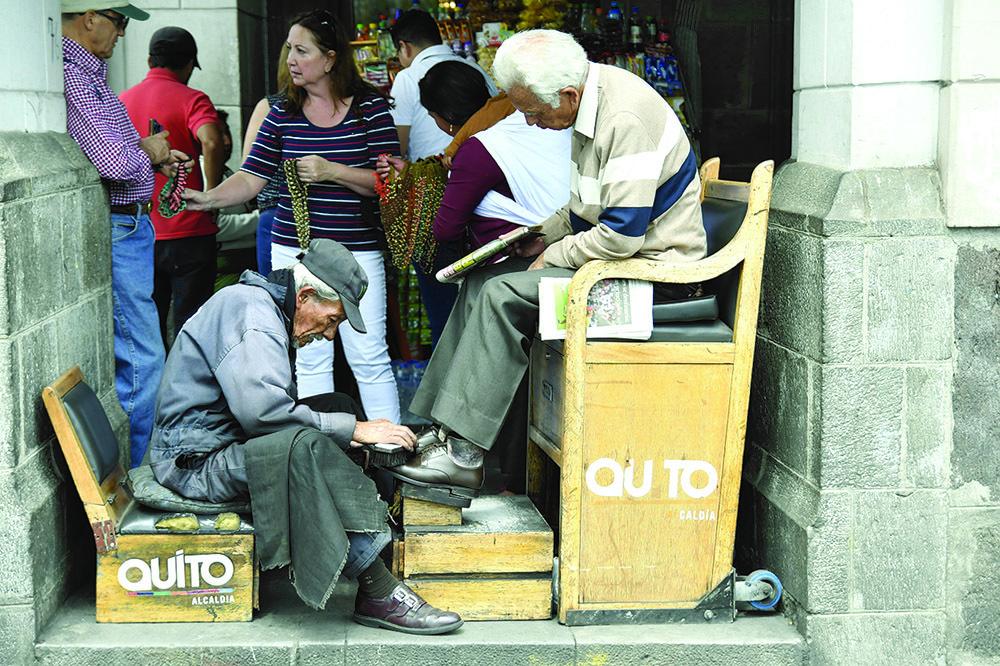 Lustrascarpe al lavoro sotto i portici di Quito (ph. Claudio Pizzin)
