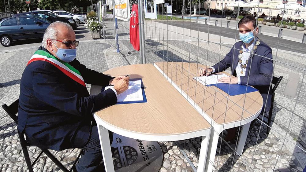I due sindaci divisi dalla rete in piazza Transalpina durante la chiusura del confine nella prima ondata della pandemia