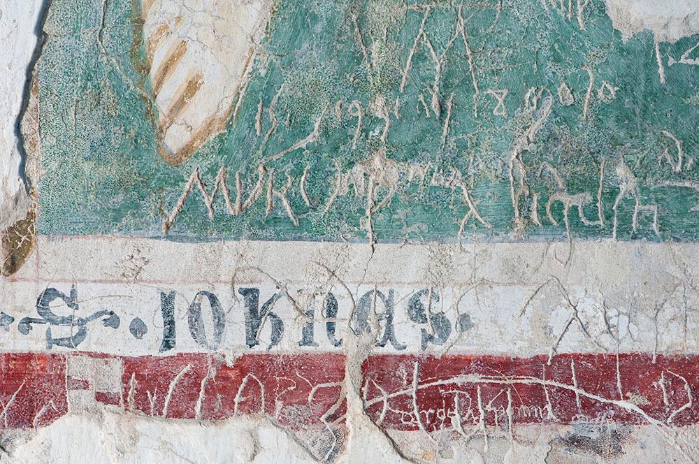 I graffiti lasciati dai fedeli e dai pellegrini sugli affreschi della cripta della Basilica (© G. Baronchelli)